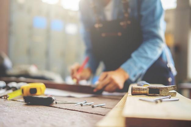 Carpinteiro que trabalha em máquinas do woodworking na loja da carpintaria. Foto Premium
