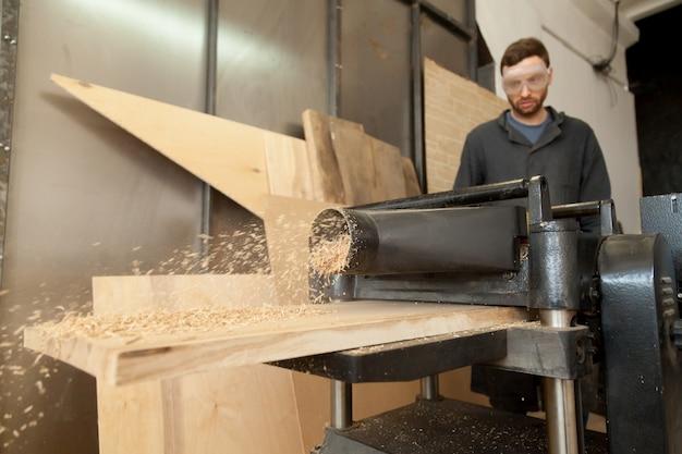 Carpinteiro que trabalha em planadora de energia estacionária com pranchas de madeira Foto gratuita