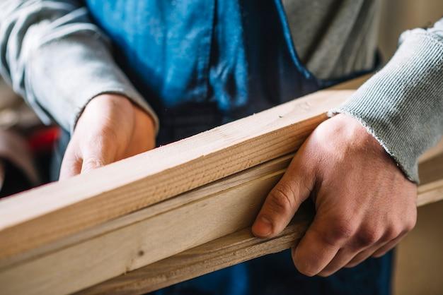 Carpinteiro que transporta madeira Foto gratuita