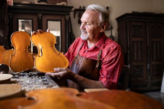 Carpinteiro sênior construindo instrumento musical de violino Foto gratuita