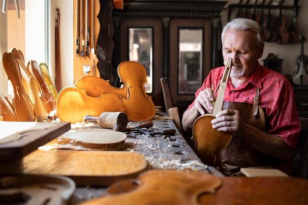 Carpinteiro sênior montando peças de instrumento de violino em sua oficina de carpinteiro Foto gratuita