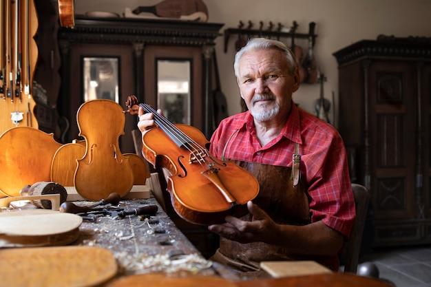 Carpinteiro sênior mostrando instrumento de violino que ele criou Foto gratuita