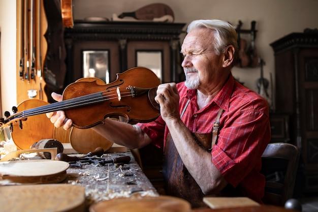 Carpinteiro sênior verificando o instrumento de violino que está prestes a consertar Foto gratuita