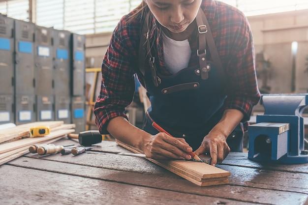 Carpinteiro trabalhando com equipamento na mesa de madeira na loja de carpintaria. mulher trabalha em uma loja de carpintaria. Foto Premium