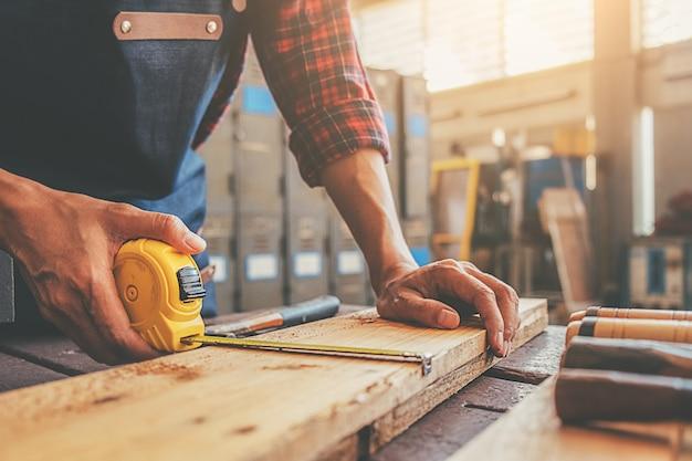 Carpinteiro trabalhando com equipamento na mesa de madeira na loja de carpintaria Foto Premium
