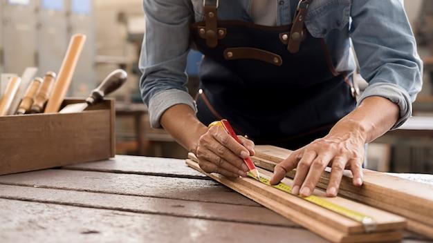Carpinteiro, trabalhando com equipamentos na mesa de madeira na carpintaria. mulher trabalha em uma carpintaria. Foto Premium