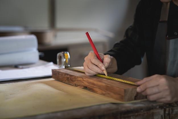 Carpinteiro trabalhando em madeira na carpintaria. o homem trabalha em uma carpintaria Foto Premium