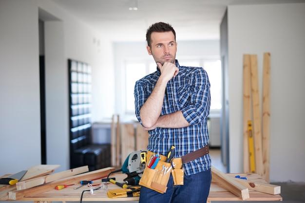 Carpinteiro trabalhando em uma casa e pensando Foto gratuita