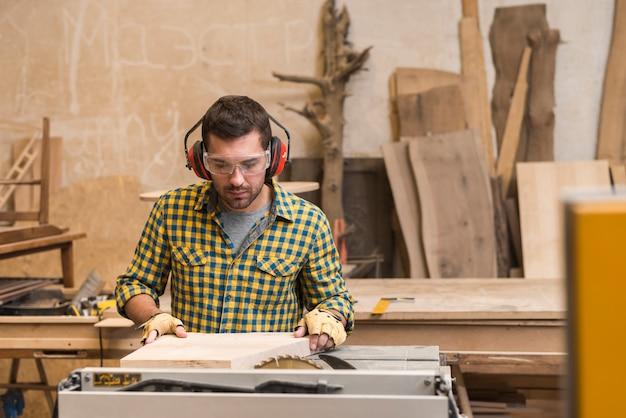 Carpinteiro trabalhando em uma serra elétrica cortando alguma placa Foto gratuita