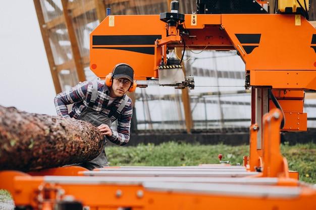 Carpinteiro trabalhando em uma serraria em uma fabricação de madeira Foto gratuita