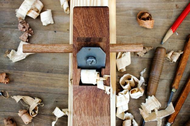 Carpinteiro trabalhando na madeira com uma plaina Foto Premium