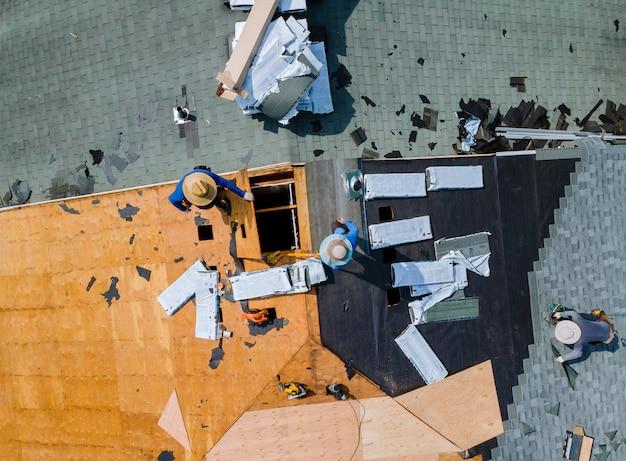 Carpinteiro trabalhando no telhado de telha de asfalto de substituição Foto Premium