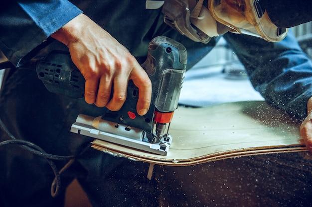 Carpinteiro usando serra circular para cortar tábuas de madeira Foto gratuita