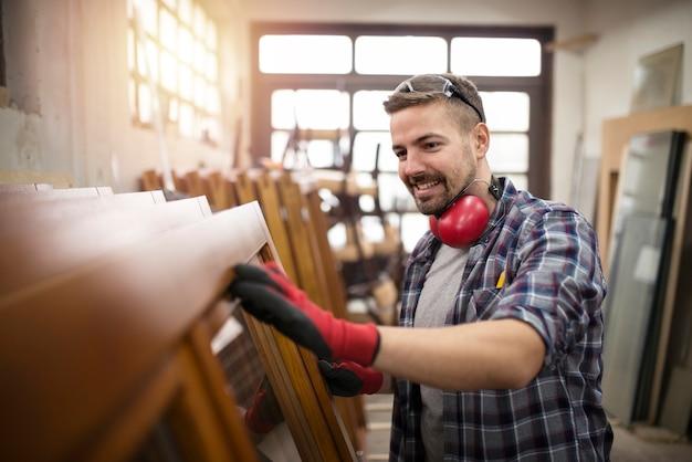 Carpinteiro verificando a qualidade de seu trabalho em carpintaria Foto gratuita