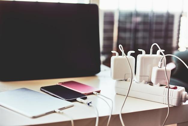 Carregadores de telefone e laptop na mesa Foto Premium
