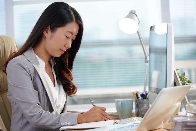 Carreira asiática, sentado à mesa no escritório e trabalhando com documentos Foto gratuita