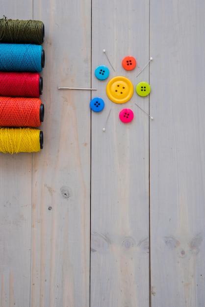 Carretéis coloridos do fio com agulhas decorativas; pinos e botões coloridos na mesa de madeira Foto gratuita