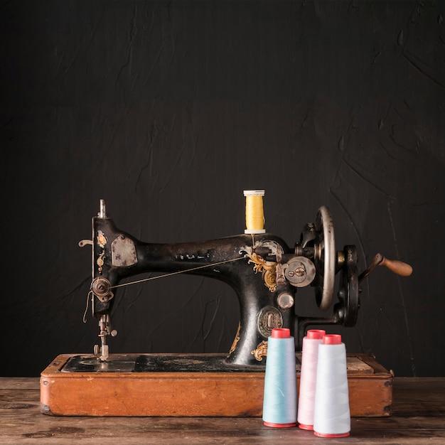 Carretéis com fio perto de máquina de costura antiga Foto gratuita