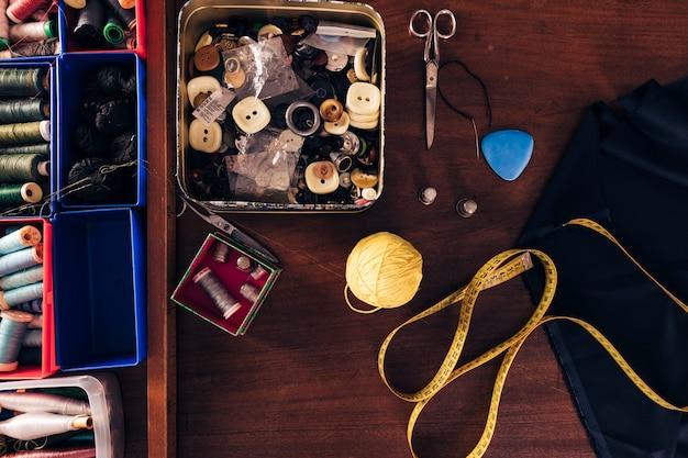 Carretéis de linhas de costura; botões; bola de lã; fita métrica; giz; tecido e tesoura na mesa de madeira Foto gratuita