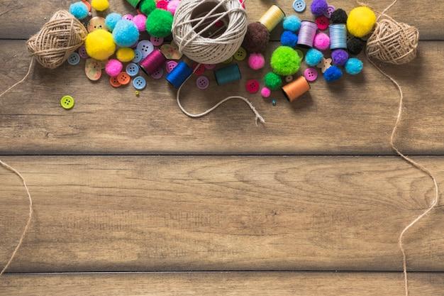 Carretel de corda; botões coloridos; carretel e bolas de algodão na prancha de madeira Foto gratuita