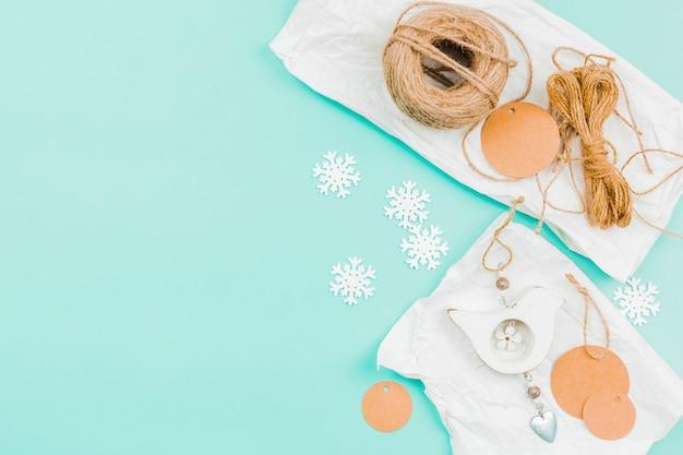 Carretel de corda de juta; círculo de papel e floco de neve para fazer a parede pendurado no pano de fundo turquesa Foto gratuita