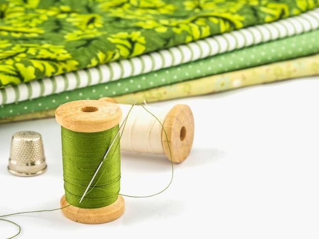 Carretel de madeira do bordado de fio definido com pano sobre fundo branco Foto gratuita