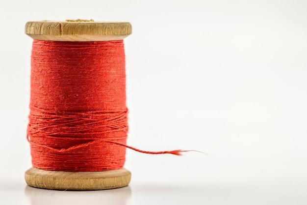Carretel ou carretel de linha de costura vermelha isolado no branco. profundidade superficial de campo. tiro macro close-up. Foto Premium