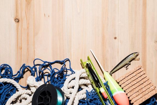 Carretilha de pesca; isca de pesca; flutuador de pesca; cortiça e rede de pesca na mesa Foto gratuita