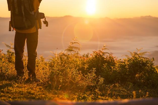 Carrinho de alpinista no acampamento perto de barraca laranja e mochila nas montanhas Foto gratuita