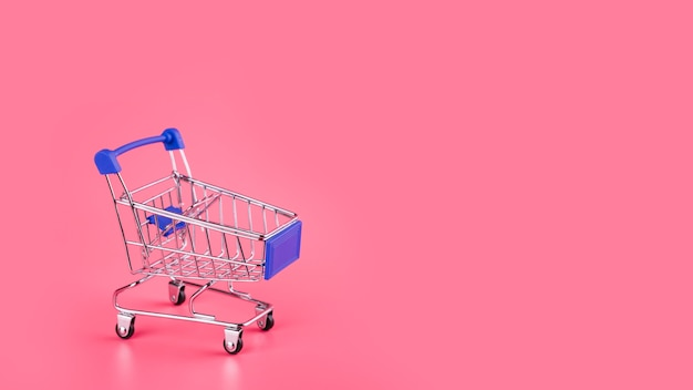 Carrinho de compras azul vazio no pano de fundo rosa Foto gratuita