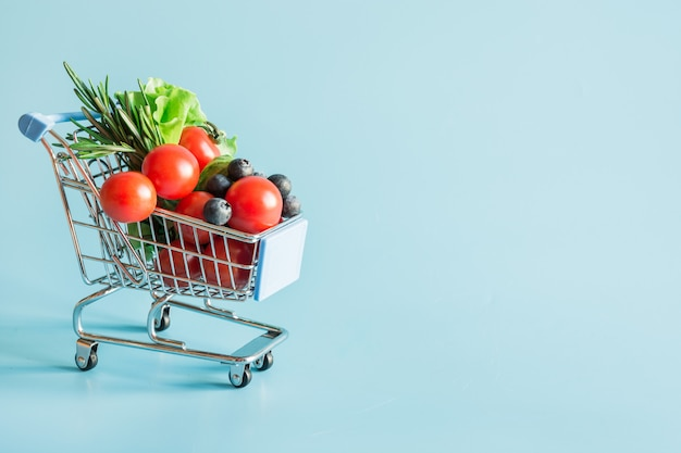 Carrinho de compras cheio de alimentos vegetais frescos Foto Premium