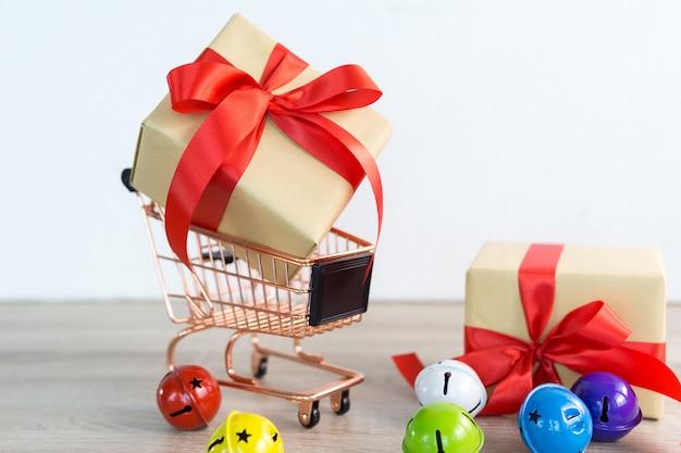 Carrinho de compras com caixa de presentes de natal fita vermelha e sino colorido em madeira Foto Premium