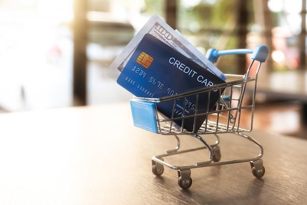 Carrinho de compras com cartões de crédito e dinheiro na mesa Foto Premium