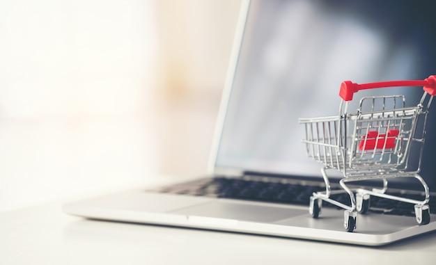 Carrinho de compras com laptop na mesa Foto Premium