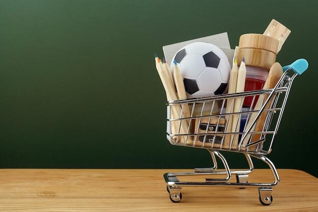 Carrinho de compras com material escolar sobre o quadro-negro verde Foto Premium