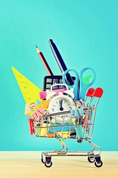 Carrinho de compras com objetos de papelaria. escritório, material escolar. Foto Premium