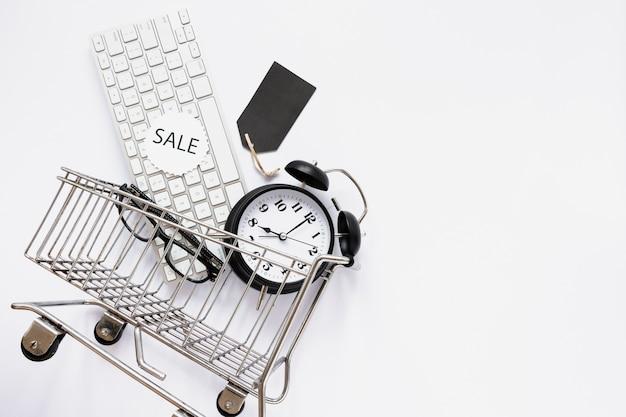 Carrinho de compras com objetos e adesivo de venda Foto gratuita