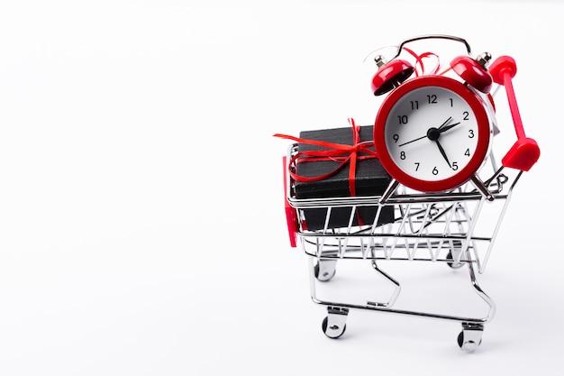 Carrinho de compras com presente e despertador Foto gratuita