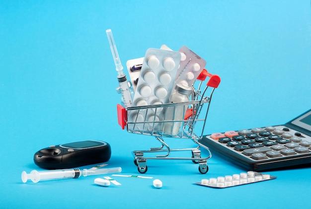 Carrinho de compras com remédios, seringas de insulina para diabetes e calculadora. Foto Premium