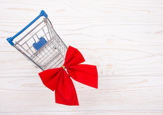 Carrinho de compras com um laço vermelho Foto Premium