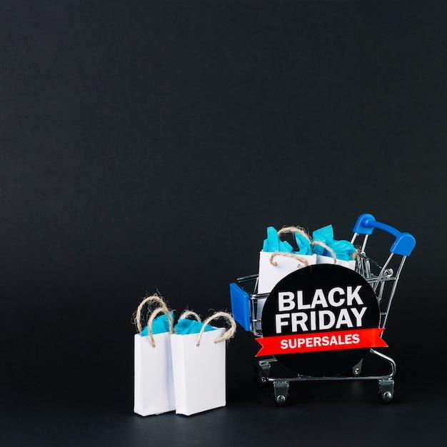 Carrinho de compras de brinquedo com presentes em pacotes e tablet Foto gratuita