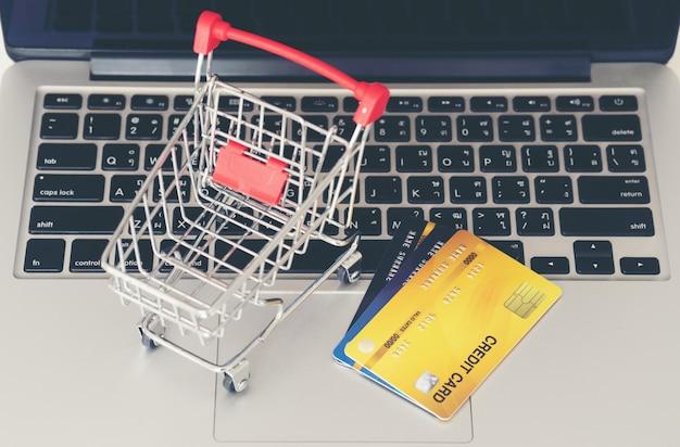 Carrinho de compras e cartão de crédito com o laptop na mesa Foto Premium