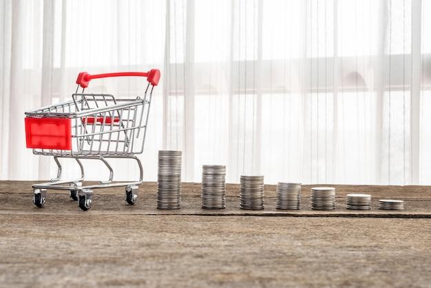 Carrinho de compras e pilhas de moedas Foto Premium