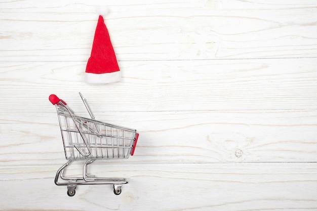 Carrinho de compras e um chapéu de papai noel em um fundo branco de madeira (conceito de venda de natal) Foto Premium