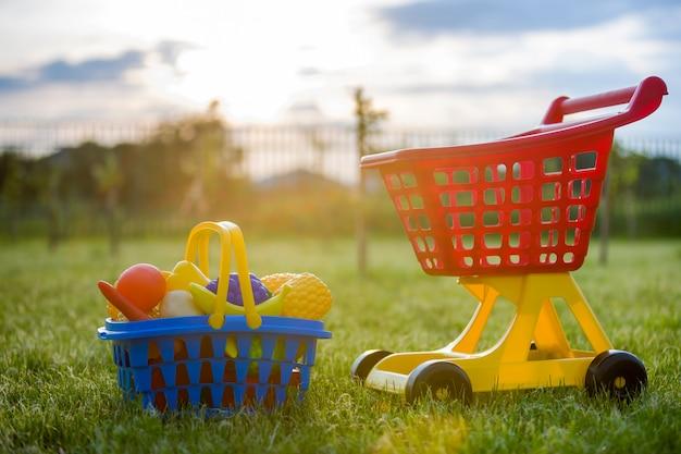 Carrinho de compras e uma cesta com frutas e legumes de brinquedo. brinquedos coloridos plásticos brilhantes para crianças ao ar livre num dia ensolarado de verão. Foto Premium
