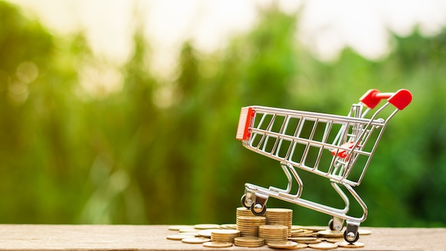 Carrinho de compras e uma pilha de moedas de ouro na mesa de madeira Foto Premium