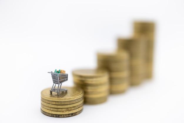 Carrinho de compras em miniatura ou carrinho em cima da pilha de moedas de ouro usadas em branco Foto Premium