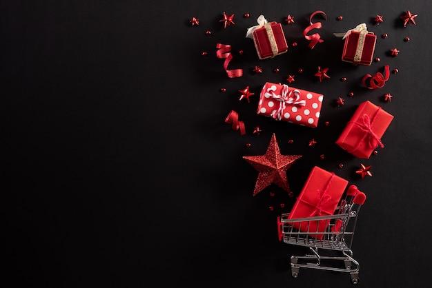 Carrinho de compras espirrar decoração de natal em fundo preto. Foto Premium
