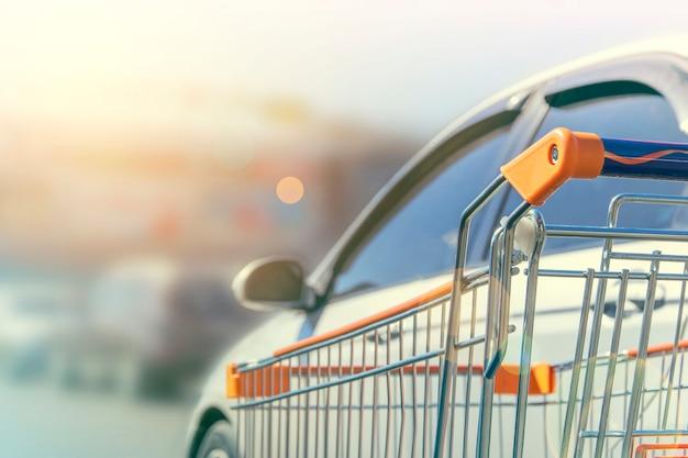 Carrinho de compras fica ao lado do carro Foto Premium