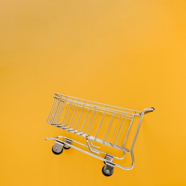 Carrinho de compras inclinado em fundo amarelo Foto gratuita